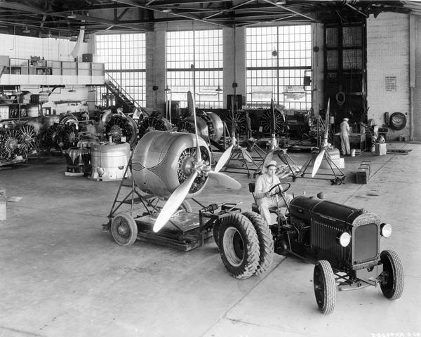 Slightly elevated view of a worker moving an airplane engine with an International I-30 industrial tractor and trailer inside the Municipal Airport hangar. The tractor was owned by American Airlines.