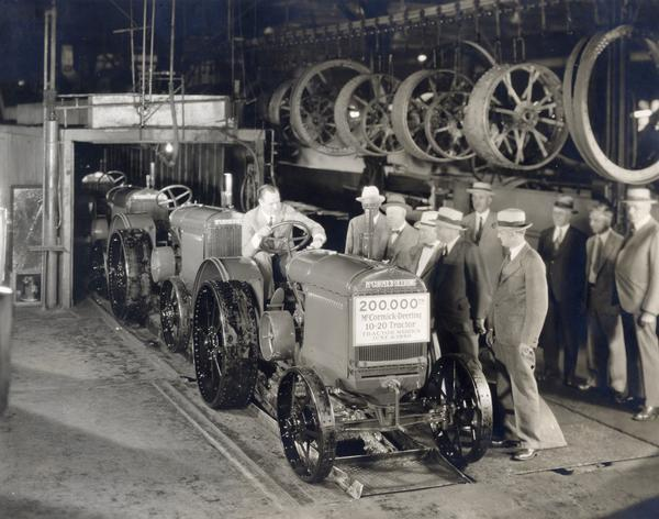 Cyrus McCormick III drives the 200,000th McCormick-Deering 10-20 tractor off of the assembly line at International Harvester's Tractor Works. Gathered for the occasion are company executives (left to right) P.F. Shryer, general superintendent, tractor production; C.H. Haney, director of foreign sales; C.R. Morrison,, assistant domestic sales manager; P.Y. Timmons, in charge of tractor and thresher sales; J.H. Waring, superintendent of Tractor Works; (rear row) J.F. Jones, director of domestic and Canadian sales; M.F. Holahan, domestic sales manager; and E.F. Bolte, Canadian sales manager.
