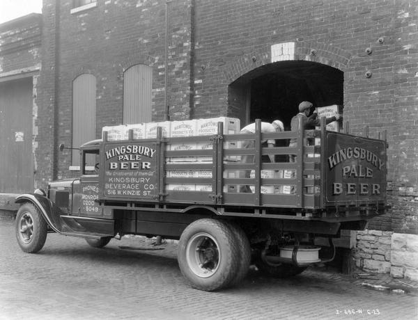 "Men loading crates of Kingsbury Pale Beer onto an International B-4 truck outside the Kingsbury Beverage Company. The truck had a 170-inch wheelbase. The wooden crates bear the name ""Manitowoc Products Co., Manitowoc, Wisconsin""."