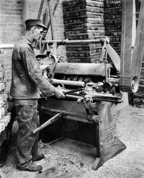 Worker turning a wagon wheel spoke on a belt-driven industrial lathe at International Harvester's Accurate Engineering Works.