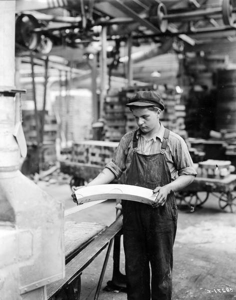 Young man - possibly a teenager - sanding a section of a wooden wagon wheel with a belt sander at International Harvester's Accurate Engineering Works.