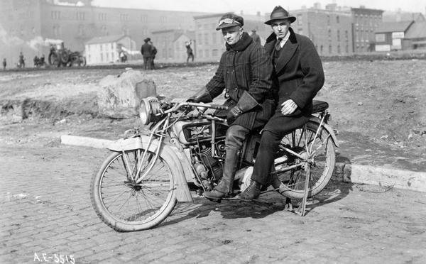 Two riders on an early Excelsior-Henderson motorcycle near a community garden at Harrison and Jefferson streets in Chicago. An International Harvester tractor is cultivating the soil in the background. The men on the motorcycle were the garden inspector and his assistant. The Excelsior-Henderson motorcycle was manufactured in Chicago until it went out of production in 1931.