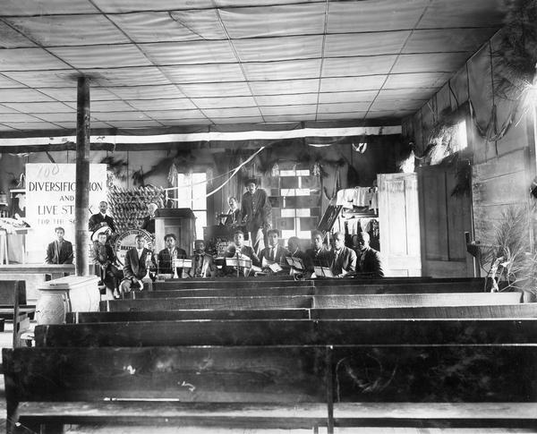 African-American school band assembled in a lecture hall at the Piney Woods Country Life School with Agricultural Extension Department workers and charts in background. Original caption notes that Professor Holden, an International Harvester Agricultural Extension lecturer, spoke at the school on March 8, 1914.