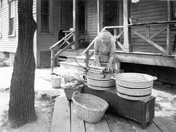 "Mrs. Eshe demonstrating the washing of laundry with a washboard, ringer and tub in front of a farm house. The original caption reads: ""Washing with no improved equipment. Mrs. Eshe posing."""