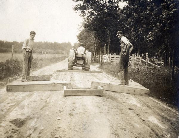 Road workers grading a rural country road with an Avery tractor and wooden grading blocks. The image was cropped from a postcard collected by International Harvester's Agricultural Extension Department to illustrate the condition of rural roads.