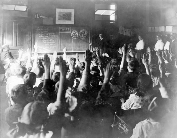 "Students are raising their arms as an instructor is discussing the merits of thrift. The instructor is pointing to chalkboard illustrations of a well groomed face and a disheveled face. The room is crowded with children and teachers. Writing on blackboard reads: ""Plan something. Make something. Save Something. Plan with parents. Plan with teachers. Plan with each other. Make money. Make prosperity. Make character. Save money. Save energy. Save people."""