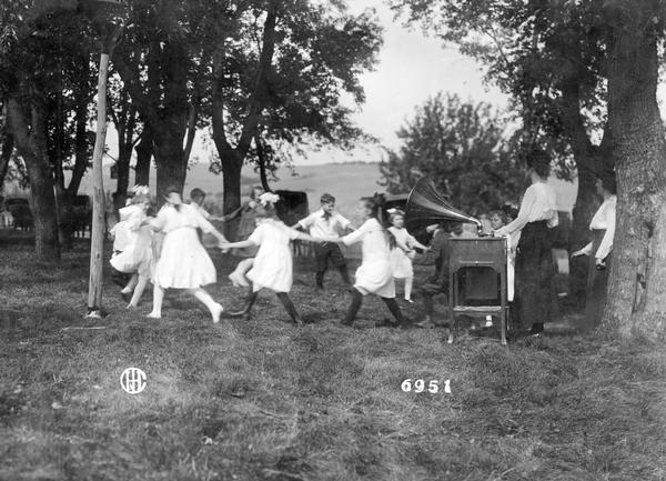 School children dancing in a circle to music from a Victrola phonograph as women look on. The children are outdoors, possibly in a rural schoolyard.