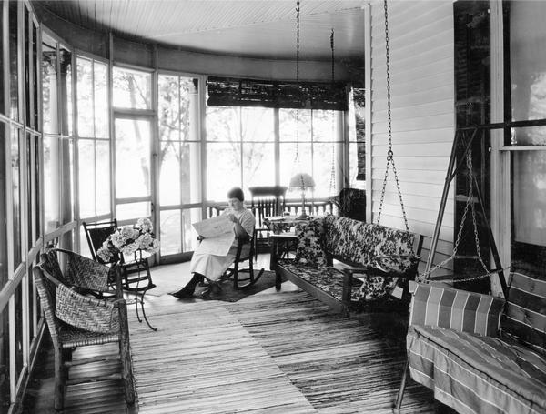 "Miss Marilla Zearing reading a newspaper on a rocking chair in the screened porch of her home. The photograph was taken for International Harvester's Agricultural Extension Department. The original caption reads: ""Home Economics - comfortable, screened-in porch."""