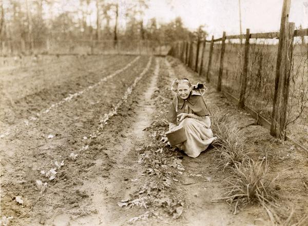 "Mrs. James M. Baker in her winter garden picking turnips. Original caption reads: ""She was pulling some winter turnips which behind her were multiplying. In front of her are seen two rows of new cabbage plants. Mrs. Baker cans enough vegetables and fruit to supply her family throughout the winter, but always has some fresh vegetables in the garden for greens."""