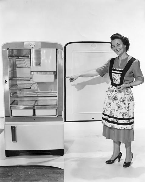"Publicity photograph of Irma Harding pointing out features of a new model refrigerator. Ms. Harding was a fictional character who acted as a  spokesperson for International Harvester refrigerators. The woman here is a model playing the role of ""Irma Harding."""
