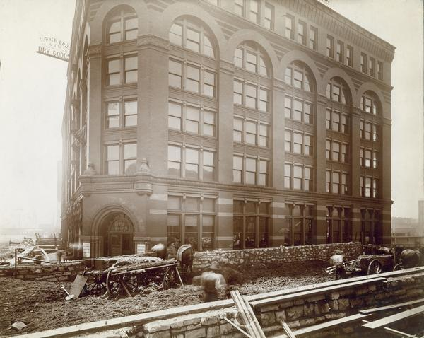 Construction work in the streets outside the offices of the McCormick Harvesting Machine Company located at 212 Market Street. Two horse-drawn wagons and several construction workers are outside the building. This building served as the McCormick Company's general office from 1885 to 1891.