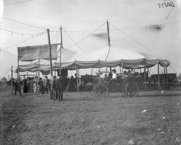 Exhibit tent featuring International Harvester's gasoline engines. Men and women are milling around the tent. One woman is sitting in an International Autobuggy.