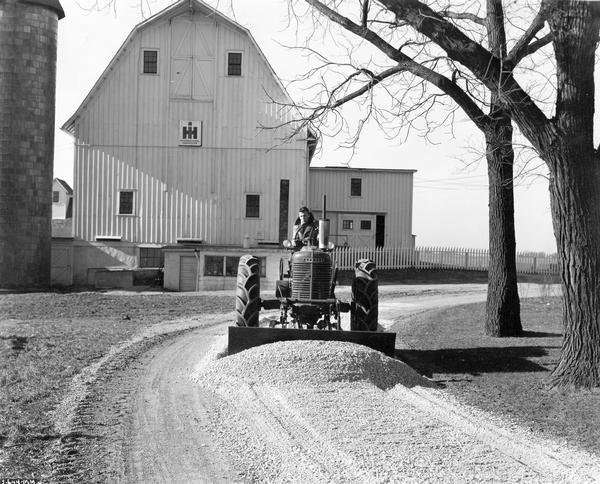 Worker leveling gravel with a McCormick-Deering Farmall M tractor and a no. 7 angle dozer at International Harvester's Hinsdale farm and testing facility.
