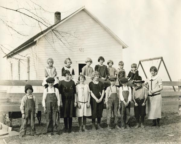 Brown Jug School students lined up along a fence outside a school house. One of the boys is wearing a cowboy hat and bandana.