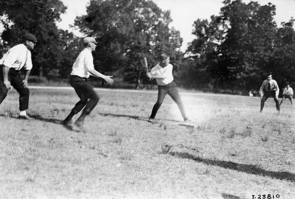 Young men playing baseball in a park or open field. The men may be employees of the International Harvester Company at a factory or office picnic.