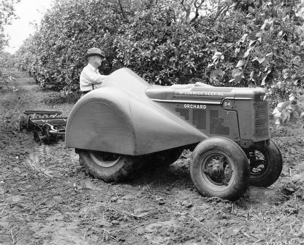 Farmer operating a McCormick-Deering O-4 orchard tractor and disc harrow.