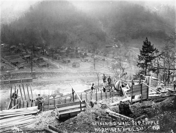 "Men working on a hillside retaining wall to ""P tipple"" of no. 2 mine. Railroad tracks and houses are below in the distance. Benham was a ""company town"" created by International Harvester for the workers of the Wisconsin Steel Company. Wisconsin Steel was a subsidiary of International Harvester and operated coal mines at Benham."