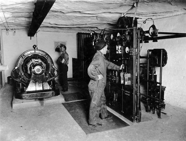 "Workers in sub-station no. 2. The workers are operating what appears to be an electric generator. Benham was a ""company town"" created by International Harvester for the workers of the Wisconsin Steel Company. Wisconsin Steel was a subsidiary of International Harvester and operated coal mines at Benham."