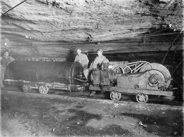 "Three miners with a mine sprinkler inside a mine shaft. Benham was a ""company town"" created by International Harvester for the workers of the Wisconsin Steel Company. Wisconsin Steel was a subsidiary of International Harvester and operated coal mines at Benham."