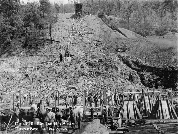 "Men working around 500 ton bin piers and tipple site of mine no. 2. Benham was a ""company town"" created by International Harvester for the workers of the Wisconsin Steel Company. Wisconsin Steel was a subsidiary of International Harvester and operated coal mines at Benham."