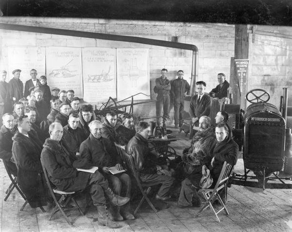 "Men seated in a makeshift classroom for an International Harvester ""tractor school"" session at A&M Motor and Implement Co. Charts illustrating the use of the ""Little Wonder"" and ""Little Genius"" tractor plows are hanging in the background. A McCormick-Deering 10-20 tractor is also present."