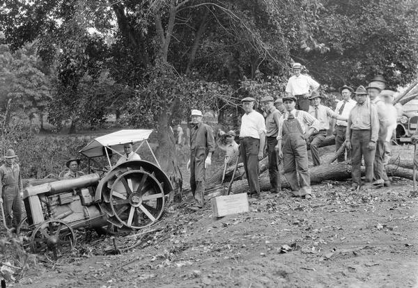 "Original caption reads: ""Members of Marshalltown Club at work on township road near Marshalltown, IA (1920). Over fifty members of the Club contributed a day's work to improving the road leading to town. For the privilege of giving this day's work, each volunteer paid $10 into the Club's special road fund, the money to be used in improving township roads, for which work the county road fund cannot be used. After these business men graded this piece of road, farmers graveled it. Thus a spirit of cooperation was established."" The men are using a Fordson tractor."