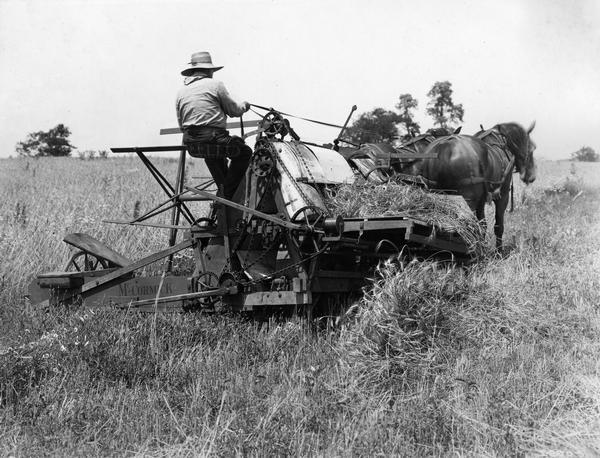 "Farmer harvesting grain with horse-drawn McCormick harvester and wire grain binder built in 1876. The scene is likely a historical re-enactment - possibly created in conjunction with International Harvester's ""reaper centennial"" celebration. Original caption reads: ""The wire binding attachment consisted mainly of two steel fingers which moved back and forth and twisted a wire band around each sheaf of grain. This machine did the cutting and binding in a single operation, requiring but one man to drive the team. McCormick built and sold 50,000 wire binders between 1877 and 1885."""