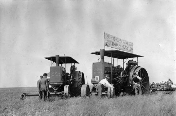 Men tending to two Aultman and Taylor tractors at the Winnipeg tractor contest in Canada. One of the tractors is a 30-60 gas tractor.