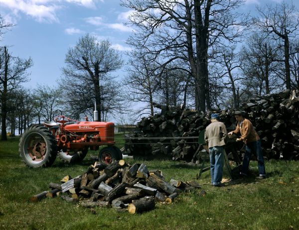 Two farmers cutting firewood with a belt-driven circular saw powered by a McCormick Farmall H tractor.