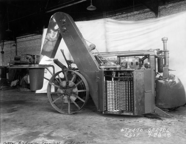 Engineering photograph of an experimental cotton picker attached to a Farmall tractor.
