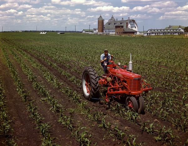 Slightly elevated view of a farmer on a McCormick Farmall H tractor with cultivator at Hinsdale Farm, near International Harvester's experimental farm.