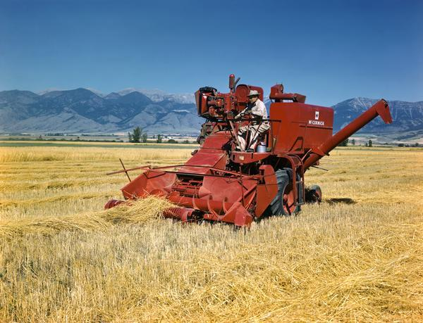 Farmer harvesting wheat with a McCormick combine (harvester-thresher) against a mountainous background. The combine is using a windrow pickup head and may be experimental.