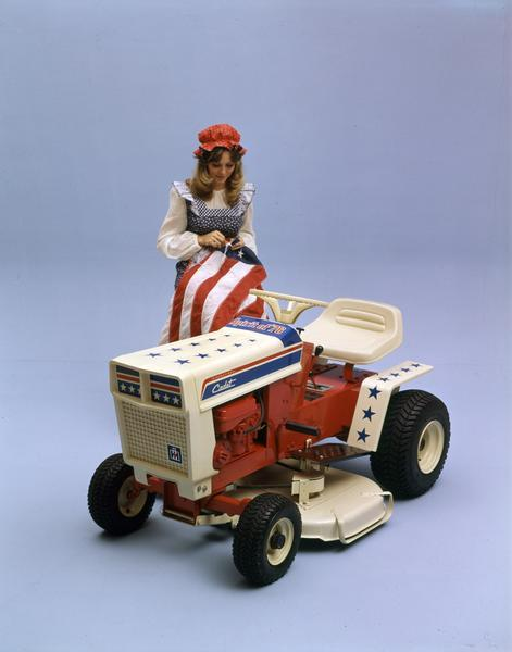 Color advertising photograph for International Spirit of '76 Cadet lawn tractor featuring a model dressed as Betsy Ross sewing stars onto a U.S. flag. The tractor was meant to commemorate the bicentennial of the United States.