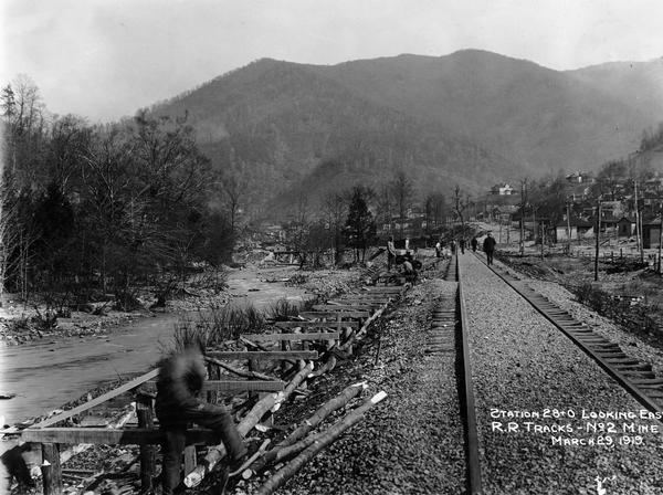 "Men building a dock along railroad tracks. The tracks run along a stream or small river. Benham was a ""company town"" created by International Harvester for the workers employed in the mines of its subsidiary, the Wisconsin Steel Company."