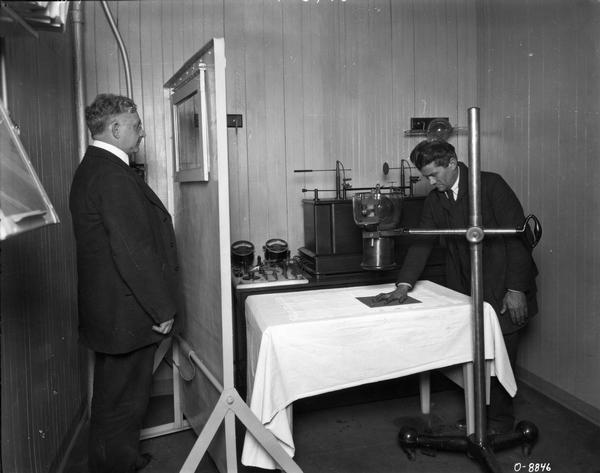 A man having his hand x-rayed as another man looks on from behind a shield. The x-ray machine is most likely part of the medical facilities at one of International Harvester's factories (works).