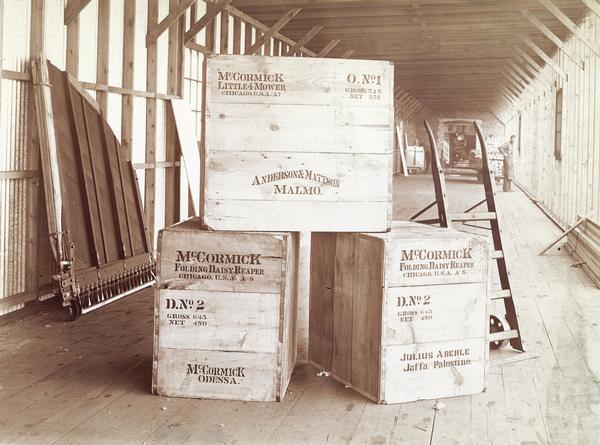 Shipping crates at the McCormick Harvesting Machine Company factory. The crates contain a Little 4 mower bound for Anderson & Mattson of Malmo, a McCormick Folding Daisy Reaper bound for Julius Aberle of Jaffa, Palestine, and another Folding Daisy Reaper bound for Odessa, Russia.
