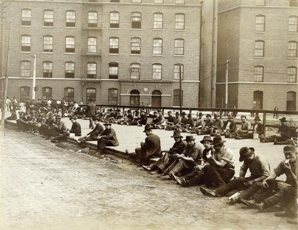 Factory workers eating lunch outside International Harvester's McCormick Works. The factory was owned by the McCormick Harvesting Machine Company before 1902.