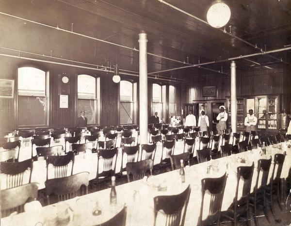 Dining hall at International Harvester's McCormick Works. The factory was owned by the McCormick Harvesting Machine Company before 1902. The staff of the dining hall are lined up in the background.