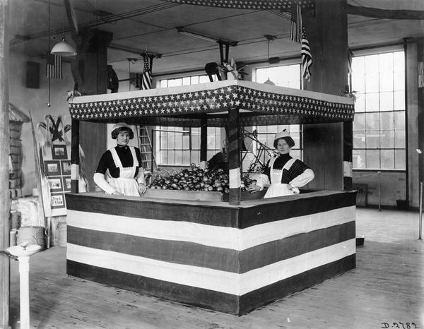 Two women staffing an apple stand for an agricultural exhibit at International Harvester's Deering Works. The stand is decorated in stars and stripes. The factory was owned by the Deering Harvester Company before 1902.