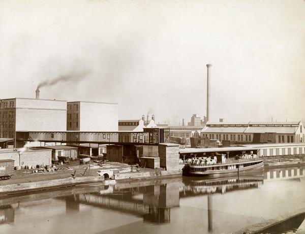 "View across water towards a boat called ""The Imperial"" moored along the dock at the McCormick Reaper Works. The boat is loaded with freight. In the background are the factory grounds, including buildings, wagons, and rail cars. The factory was owned by the McCormick Harvesting Machine company before 1902. In 1902 it became the McCormick Works of the International Harvester Company. The factory was located at Blue Island and Western Avenues in the Chicago subdivision called ""Canalport."" It was closed in 1961."