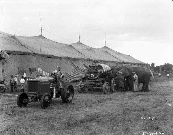 Elephants drinking water from a wagon pulled by a McCormick-Deering industrial tractor outside a circus tent belonging to the Sells-Floto Circus. Circus workers and children are standing near the tent.