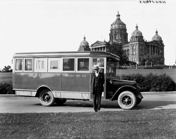 "Man posing with an International tour bus in front of the Iowa State Capitol building. The sign painted on the side of the bus reads: ""Seeing the US."""