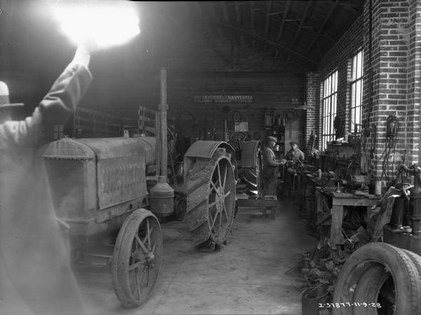 "View towards a photographer or an assistant holding a flashbulb as a photograph is taken of repairmen working on tractors in the shop of an International Harvester dealership — possibly the ""Twin-City Implement Company."""