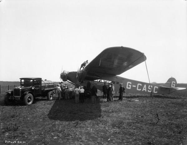 Workers refueling an airplane from an International gas truck as a small crowd is looking on. The airplane was owned by Western Canada Airways. The truck was owned by North Star Oil, Limited.