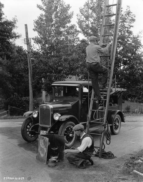 Telephone line repairmen preparing to work on a residential line. One is climbing a ladder and the other is setting up a soldering unit. Their International service truck is parked in the background.