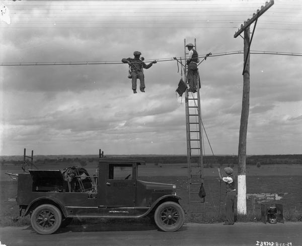 A crew of telephone line repairmen working on a rural line with their International truck parked below them.