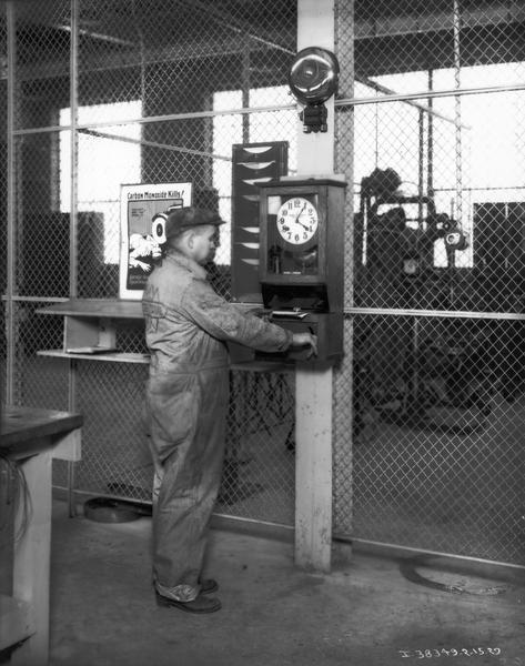 "Mechanic punching a ticket at a time clock for a service job at one of International Harvester's motor truck branch service stations. A poster warning of the danger of carbon monoxide is hanging to the worker's left. The man is wearing a jumpsuit with the International ""triple diamond"" logo."