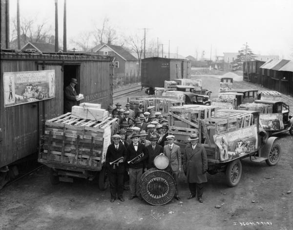 Elevated view of the Commercial Club Band posing at a rail yard with a newly arrived shipment of McCormick-Deering ball-bearing cream separators. The cream separators have been unloaded in crates onto International trucks. Large advertising posters for McCormick-Deering cream separators are mounted on the side of the rail car and on one of the trucks. The event likely was arranged by an International Harvester dealer as a public relations event.