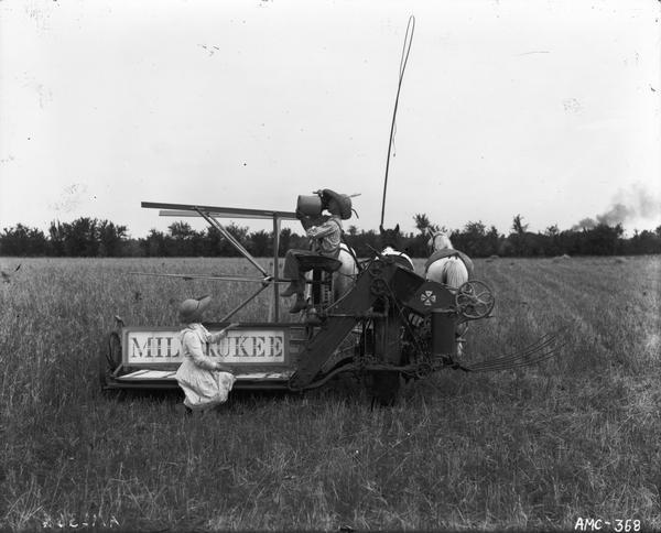 Young girl and boy posing with a horse-drawn Milwaukee grain binder in a field. The boy is drinking from a jug.