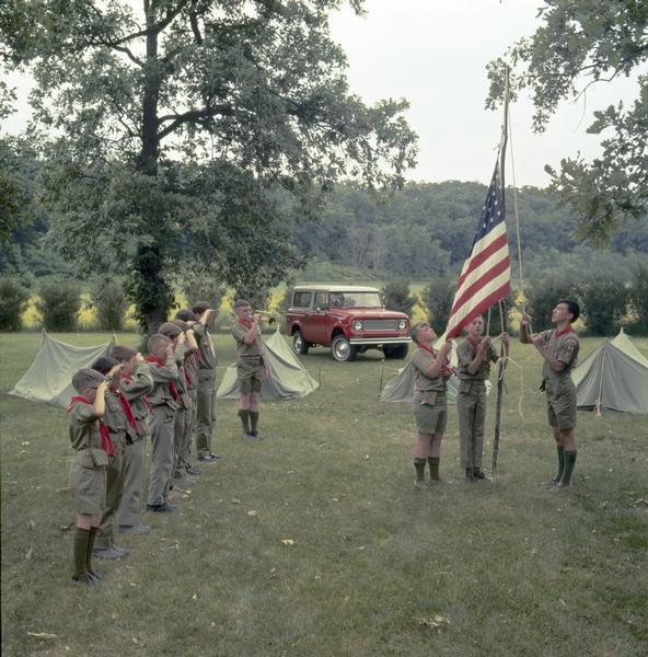 Color photograph of Boy Scouts raising a flag as others stand at attention during a ceremony. Tents and a 1972 International Scout pickup are in the background.